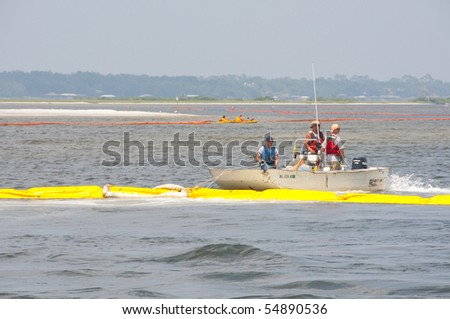 ORANGE BEACH, AL - JUNE 8: Protective oil boom is being positioned on June 8, 2010 in Perdido Pass in Orange Beach, AL as the BP oil slick threatens wildlife and tourism. - stock photo