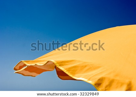 Orange beach umbrella over blue sky background. Space for copy. Jpeg file with clipping path included. - stock photo