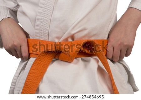 orange belt and hands of the young sporstmen in a kimono on a white background - stock photo