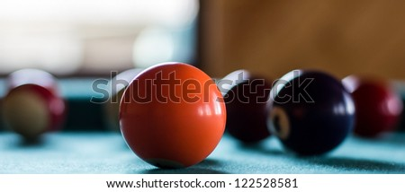Orange billiard ball before  group of others. - stock photo