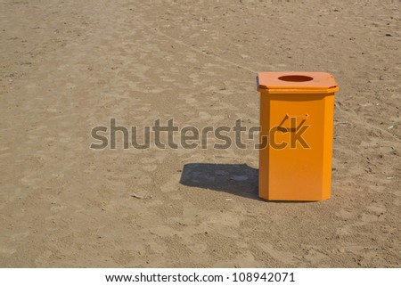 Orange bin  standing in the middle of beach - stock photo