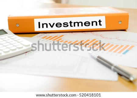 Orange  binder investment on desk in the office with calculator and pen