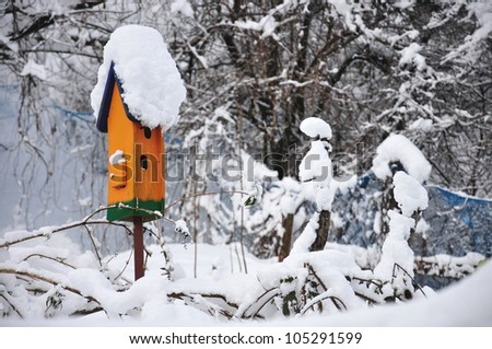 orange birdhouse covered with snow - stock photo