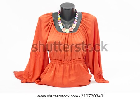 Orange blouse on mannequin with matching accessories. Elegant blouse on tailor's dummy with matching colorful necklace - stock photo