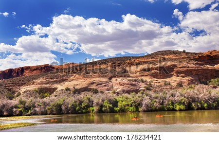 Orange Boats Colorado River Reflection Green Grass Red Rock Canyon Outside Arches National Park Moab Utah USA Southwest.  - stock photo