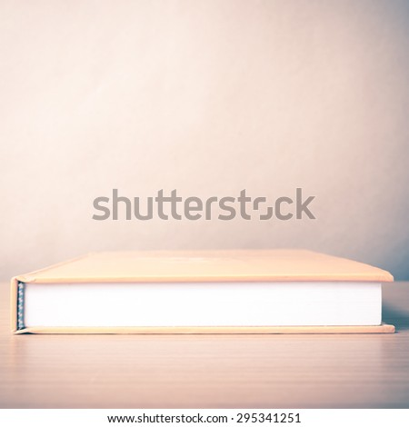 orange book on wood table background vintage style