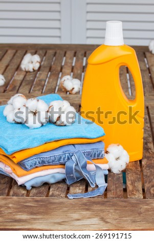 orange bottle of detergent and pile of cotton clothes on wooden table - stock photo