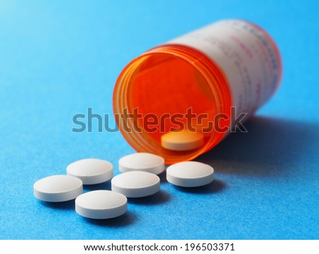 Orange bottle with white pills on blue background, focus on nearest. - stock photo