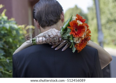 orange bridal bouquet and the couple