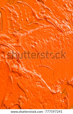 orange brush strokes of oil paint on the palette