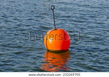 Orange buoy in  sea on water - stock photo