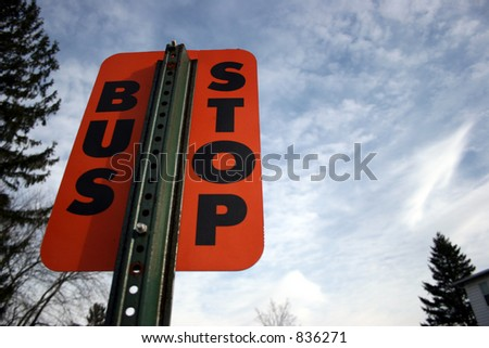Orange bus stop sign against sky. - stock photo