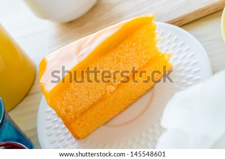 Orange cake in white dish on the wood table