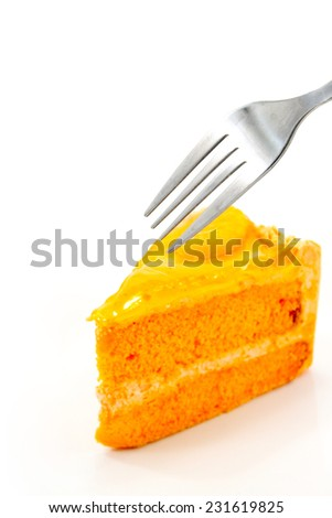 Orange cake with fork on white plate
