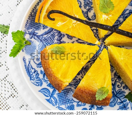 Orange cake with orange slices upside down with honey and natural vanilla. On the bright blue painted plates and a white lace tablecloth. Selective focus. - stock photo