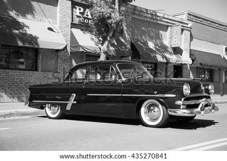 ORANGE/CALIFORNIA - APRIL 24, 2016: A classic 1953 two-door Ford with a V8 parked along side the road in the City of Orange, California USA