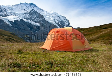 orange camping tent on autumn meadows in swiss alps, kleine scheidegg range, swiss - stock photo