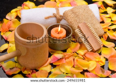 Orange candle in bowl ,towel,spoon  and rose petals background - stock photo