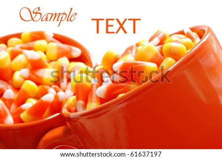 Orange ceramic mugs filled with candy corn on white background with copy space.  Macro with shallow dof. - stock photo