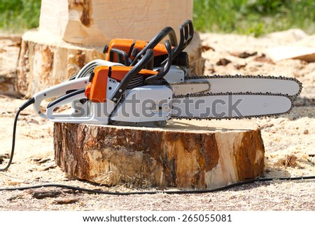 Orange chainsaws  standing on a tree stump - stock photo