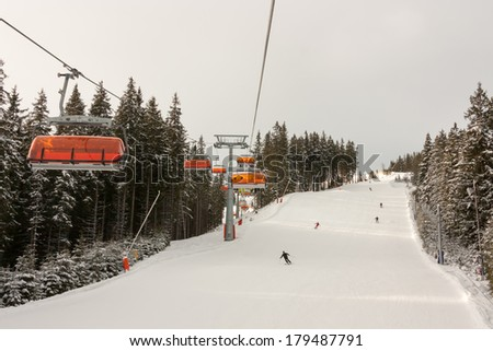 Orange Chair lifts in Jasna and skiers on slope, best Ski Resort in Slovakia.