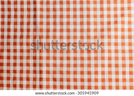 Orange checkered tablecloth texture background - stock photo