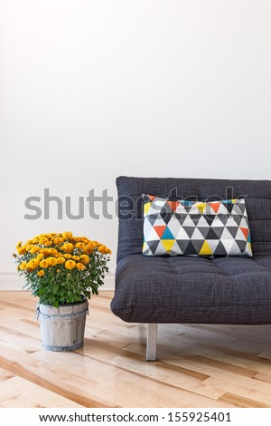 Orange chrysanthemums and gray sofa decorated with bright cushion. - stock photo