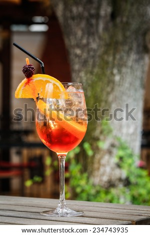 orange cocktail drink in front of a green tree on a garden table - stock photo