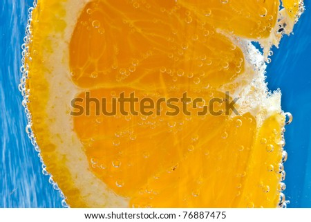 Orange cocktail - in soda water - against an ultramarine blue background