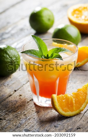 Orange cocktail on rustic wooden table - stock photo