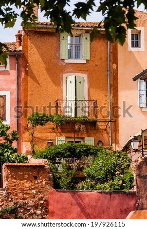 Orange colored stone buildings with lush garden in France. - stock photo