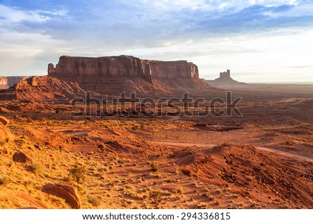 Orange colours during sunrise in this iconic view of Monument Valley, USA - stock photo