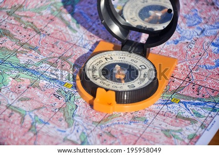 Orange compass mirror cover lies on topographic maps. Compass on the map