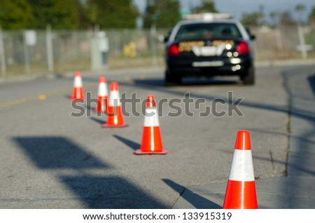 orange cones set up to direct traffic around a police car at a collision scene. - stock photo