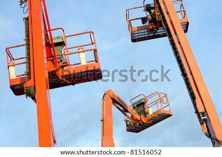 Orange construction crane baskets against blue sky - stock photo