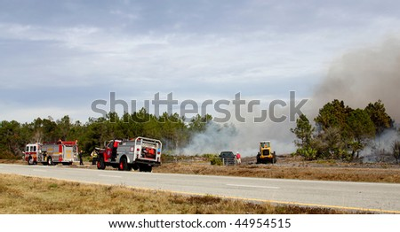ORANGE COUNTY, FL - JANUARY 8: Orange County and Florida Forestry Service fire fighters and their equipment stand by a controlled brush / forest fire on January 8, 2010 in Orange County, FL. - stock photo