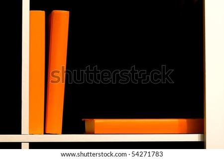 Orange covered books on a white shelf - stock photo