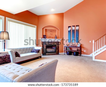 Orange cozy living room with carpet floor, white wood stairs, grey furniture and fireplace. Decorated table with candles and wood wall handmade art - stock photo