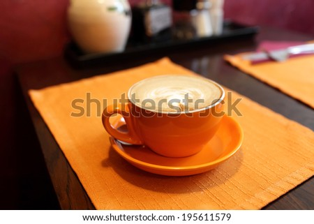 Orange cup of cappuccino in the cafe - stock photo