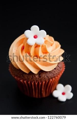 Orange cupcake on black background - stock photo