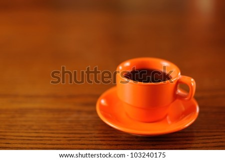 Orange demitasse coffee cup and saucer on a wooden table. Shallow DOF. Space for copy. - stock photo