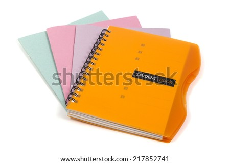 Orange diary lying on a stack of of multicolored school notebooks isolated on white background - stock photo