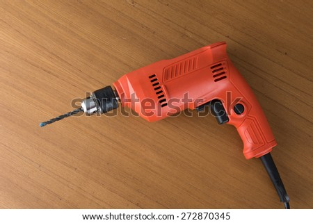 orange drill on wood background - stock photo