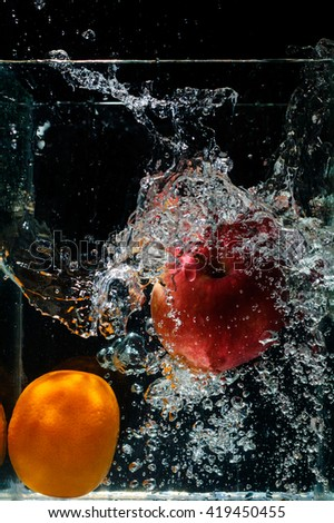 orange dropped in fish tank filled with water. - stock photo