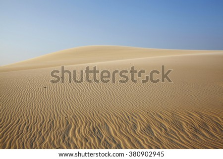 Orange dune, rippled sand going far under blue sky, Vietnam - stock photo