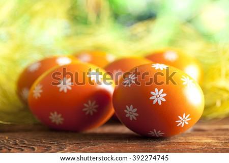 Orange Easter eggs on wooden table - stock photo