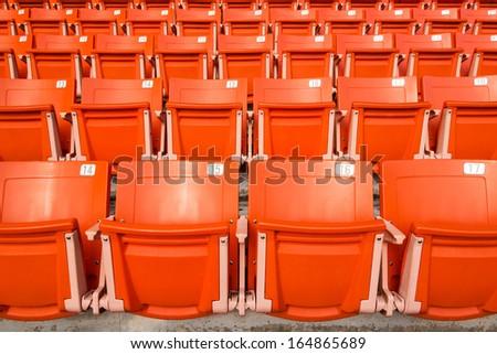 Orange empty stadium seats in stadium - stock photo