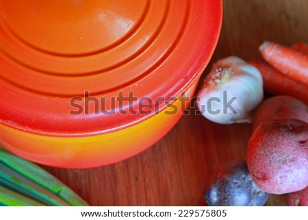 Orange enamel dutch oven on wood cutting board with potatoes, carrots & scallions arrayed