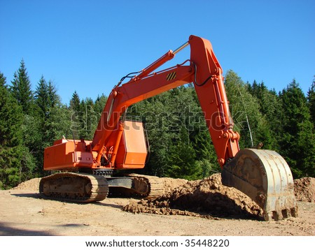 orange excavator at the forest and blue sky - stock photo