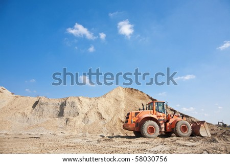 Orange excavator on a construction site working on a pile of gravel. General construction scene - stock photo
